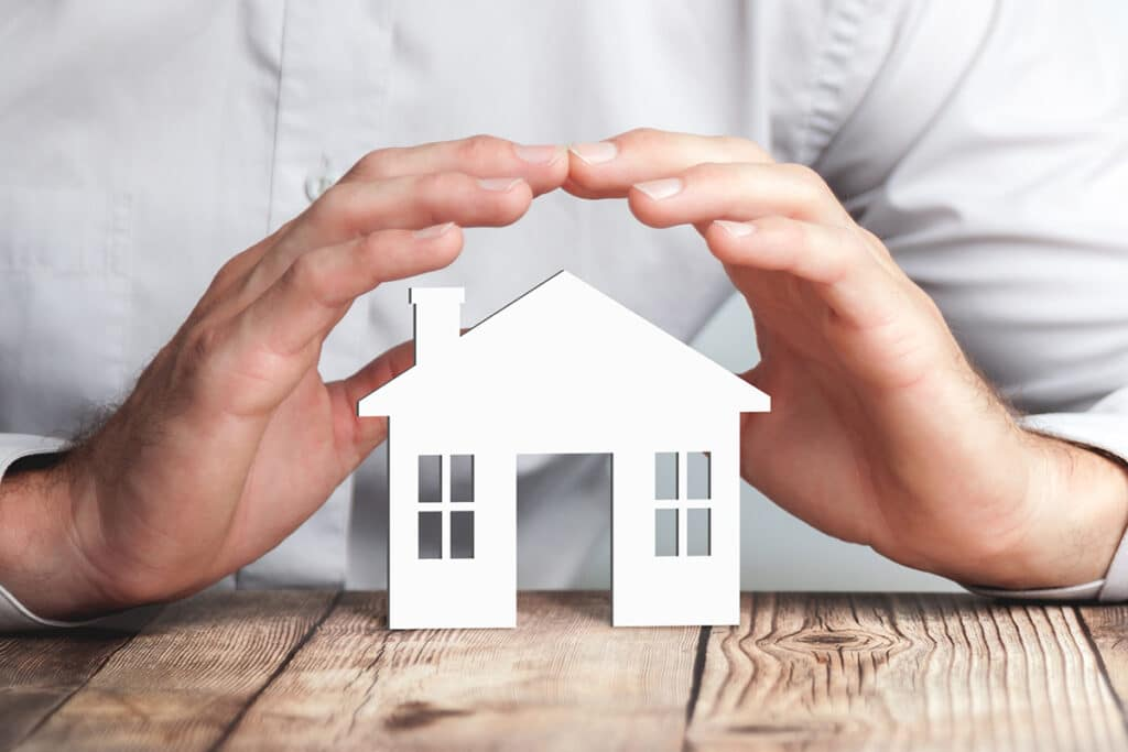 Man putting hands around cardboard house